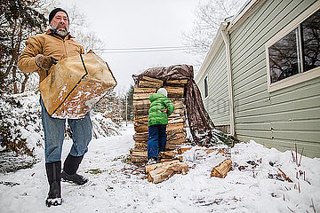 A young child helps his father collect wood from large stack in snow