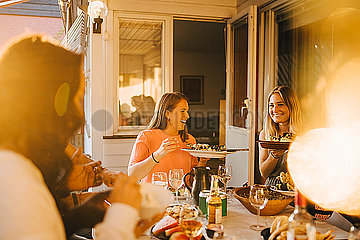Happy friends enjoying food at dining table in dinner party