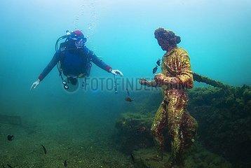 Scuba diver swimming by the submerged statue of greek God Dionysus. Baia (Baiae)  Campi Flegrei (Phlegraean Fields)  Campania