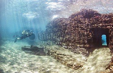 Scuba diver swimming through submerged ancient Roman building ruines. Dragonara caves  Miseno. Campi Flegrei (Phlegraean Fields)