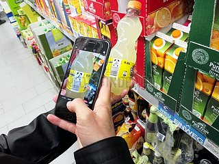 Kunde mit Smartphone im Supermarkt