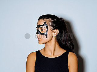 Close-up of woman with face paint looking away standing against wall