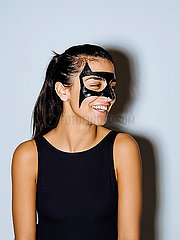 Close-up of happy woman with face paint looking away standing against wall