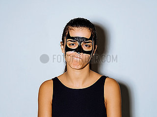 Close-up portrait of woman with black paint making face while standing against wall