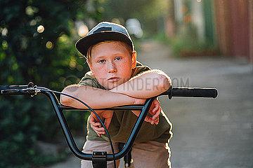 Portrait of boy with bmx bike on road