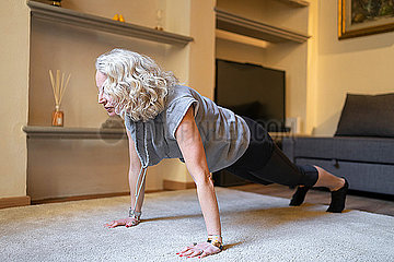 Mature woman doing Yoga exercise in the living room