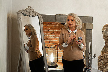 Portrait and mirror image of mature businesswoman with beauty mirror