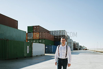 Manager in front of cargo containers on industrial site