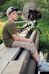 Serious boy woith bmx bike sitting on boardwalk