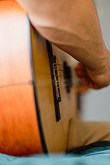Close up of male hands playing classic guitar indoors