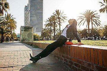 Young woman sitting on a wall  enjoying sunlight