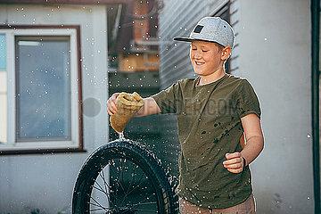 Happy boy cleaning bmx bike on yard