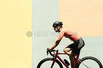 Cyclist on bicycle against a colorful wall