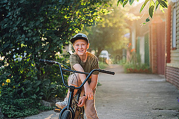 Portrait of smiling boy with bmx bike on road