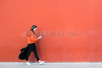 Young dancer walking and using the phone and headphones in front of a red wall