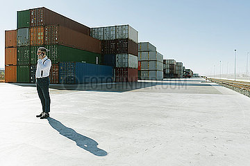 Manager talking on cell phone in front of cargo containers on industrial site