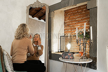 Mirror image and back view of mature businesswoman applying makeup