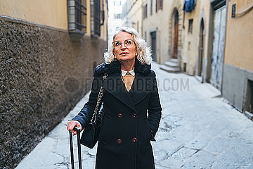 Portrait of mature businesswoman wearing black coat standing in an alley with rolling suitcase