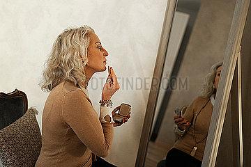 Profile of mature businesswoman applying makeup