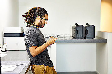 Side view of confident businessman using smart phone while standing by table in office