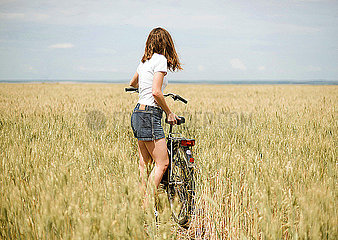 Girl with a bicycle looks at the horizon in summer