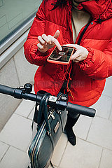 Low section of female commuter scanning QR code on electric push scooter handlebar with smart phone