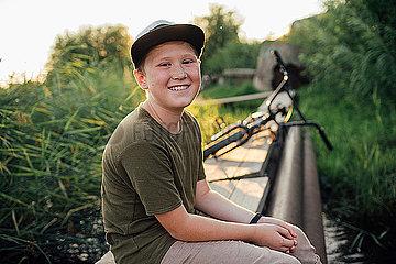 Portrait of smiling boy with bmx bike sitting on boardwalk