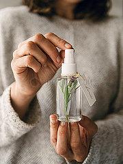 Frau hält Sprühflasche mit Lavendel
