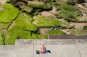 Sydney  Australien  Mann sonnt sich am Ufer des Bondi Beach