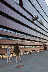 Zwei junge Frauen fotografieren Fassadenkletterer am Nationalen Forum fuer Musik in Breslau