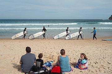 Sydney  Australien  Familie im Sand am Strand von Bondi Beach und Surfer am Ufer