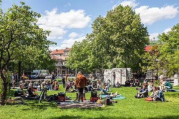 Strassenmusiker gibt Konzert auf einer Wiese am 1. Mai in der Schlesischen Strasse in Berlin-Kreuzberg