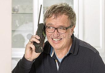 Mann telefoniert mit Siemens C4  fruehes Mobiltelefon  1992