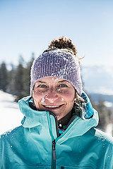Portrait einer jungen Frau mit Mütze im Schnee