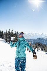 Junge Frau wirft Schneeball vor Bergkulisse