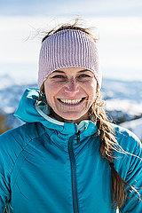 Portrait einer jungen Frau mit Stirnband vor Bergkulisse