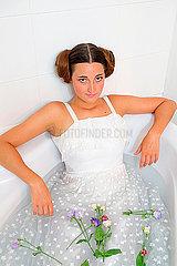 Frau in weißem Kleid in der Badewanne mit Blumen