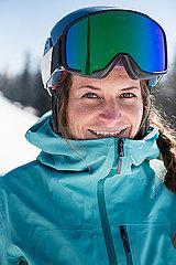Portrait einer jungen Frau mit Skibrille im Schnee