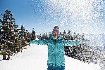Junge Frau albert im Schnee herum