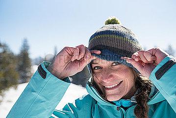 Junge Frau mit Mütze im Schnee