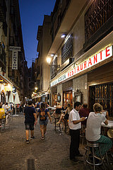 Gasse mit Restaurants fuer Touristen in Granada