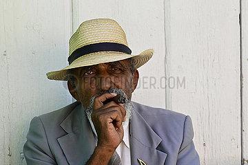 Kuba  Trinidad - Kubaner raucht eine Zigarre vor seinem Haus