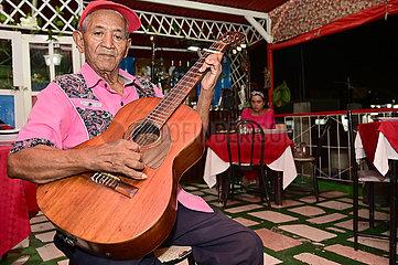 Kuba  Santiago de Cuba- Kubaner spielt in einem Restaurant fuer die Gaeste Gitarre