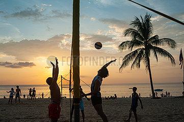 Phuket  Thailand  Einheimische spielen am Strand von Karon Beach Volleyball im Sonnenuntergang