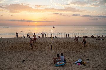Phuket  Thailand  Touristen spielen am Strand von Karon Beach Volleyball im Sonnenuntergang