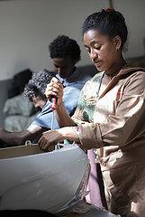 Junge Frau schraubt an einer Verkleidung