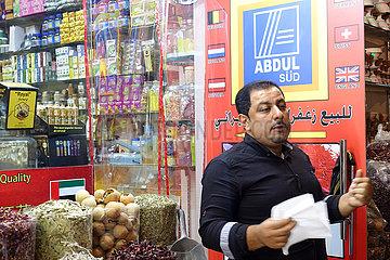 Dubai  Vereinigte Arabische Emirate  Haendler in einem Souq steht vor seinem Ladenschild Abdul Sued