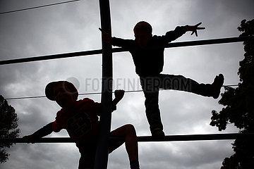 Berlin  Deutschland  Silhouette  Jungen spielen auf einem Klettergeruest