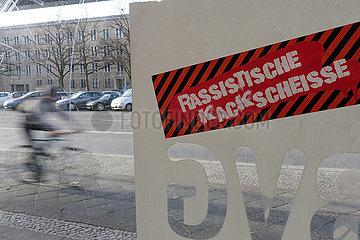 Berlin  Deutschland  Sticker mit der Aufschrift Rassistische Kackscheisse klebt an einem BVG-Wartehaeuschen