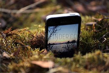 Hovmantorp  Schweden  Sonnenuntergang an einem See wird mit einem Mobiltelefon gefilmt